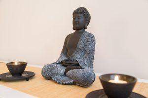 Buddhastatue in schwarz mit Kerzen im Shiatsuraum als Symbol für die Seite Impressum