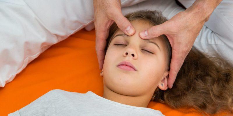 Shiatsutechnik mit Daumen auf der Stirn zur Entspannung bei einem Kind