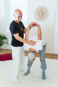 Dehnung mit Vorbeugen aus dem Stand und Verschränkung der Hände hinter dem Rücken