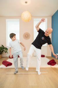 Shiatsupraktiker zeigt die Übung am Stock gehen für ein Kind